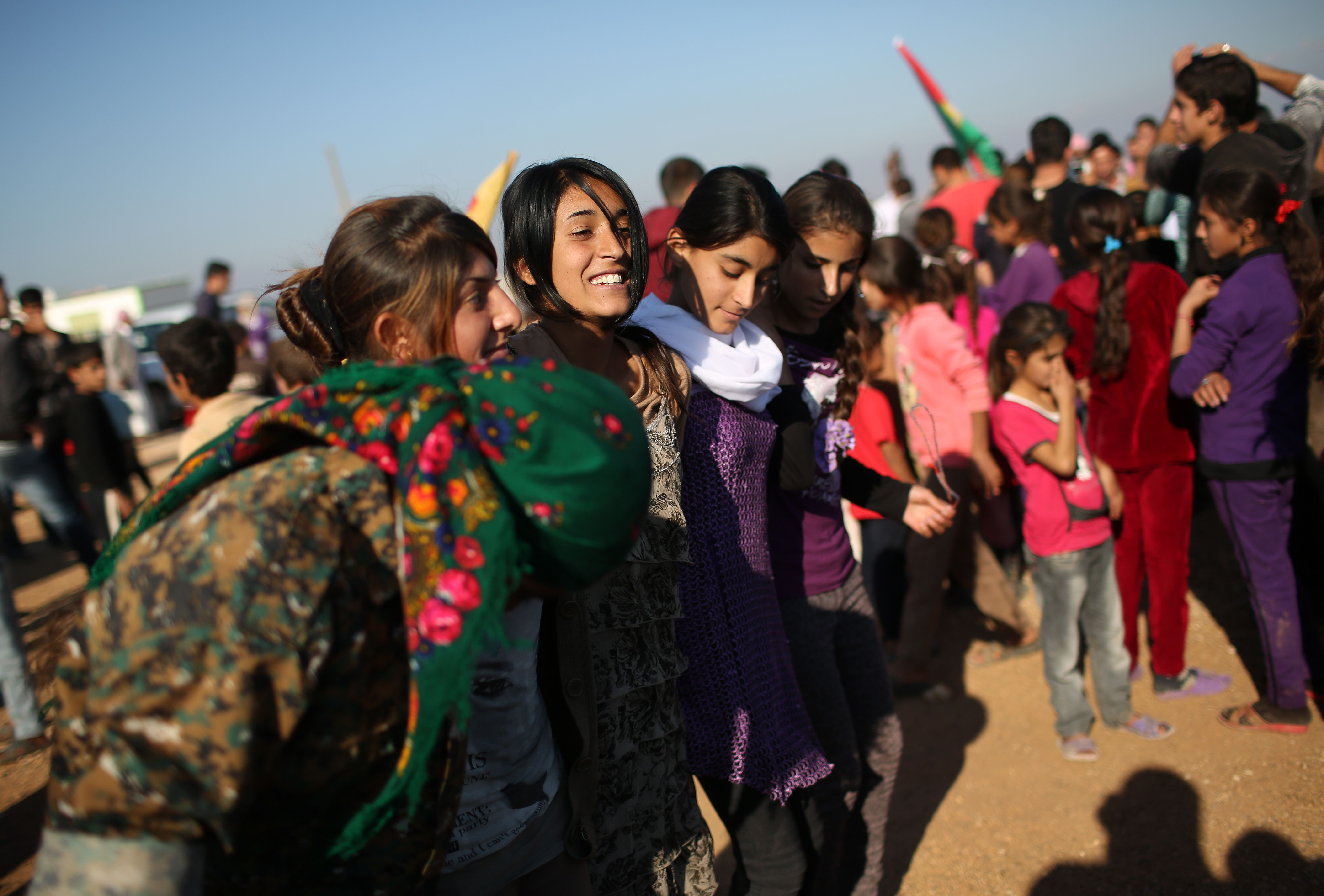 DEREK, SYRIA - NOVEMBER 13: Yazidi refugees celebrate news of the liberation of her homeland of Sinjar from ISIL extremists, while at a refugee camp on November 13, 2015 in Derek, Rojava, Syria. Kurdish Peshmerga forces in Iraq say they have retaken Sinjar, with the help of airstrikes from U.S. led coalition warplanes. The Islamic State captured Sinjar in August 2014, killing many and sexually enslaving thousands of Yazidi women. (Photo by John Moore/Getty Images)